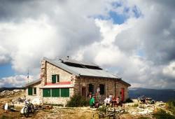 Il rifugio Sebastiani dall'esterno con diversi gruppi di escursionisti a godersi la bella giornata
